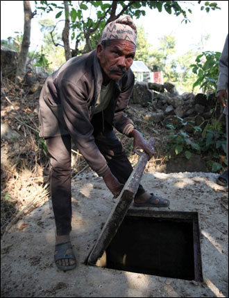 Hasta Bahadur B.K inspects the MUS holding tank in his village of Lekhparajul, Surkhet.