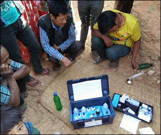 Photo: Members o fBasbot MUS Water User Group in Jumrikada, Pyuthan observe as the PAHAL technicial takes water samples using a field water quality testing kit.